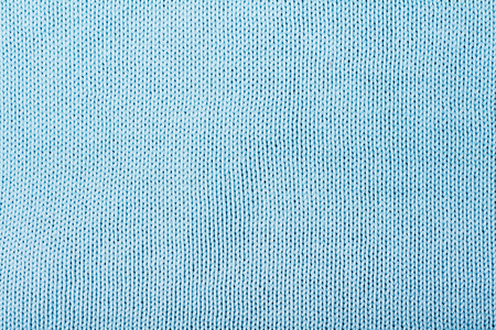 Sweater or scarf fabric texture large knitting. Knitted jersey background with a relief pattern. Wool hand- machine, handmade, blue. Stock Photo