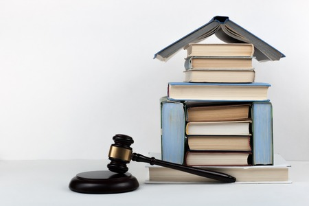 Het open boek van het wetsconcept met houten rechtershamer op lijst in een rechtszaal of wetshandhavingsbureau, witte achtergrond. Ruimte voor tekst kopiëren.
