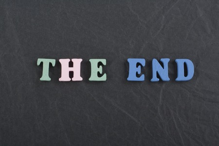 THE END word on black board background composed from colorful abc alphabet block wooden letters, copy space for ad text. Learning english concept.