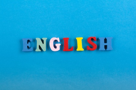 assignments: English word on blue background composed from colorful abc alphabet block wooden letters, copy space for ad text. Learning english concept.