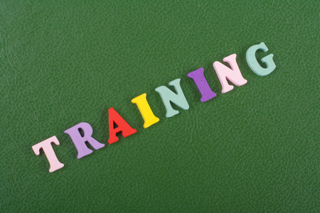 TRAINING word on green background composed from colorful abc alphabet block wooden letters, copy space for ad text. Learning english concept. Stock Photo
