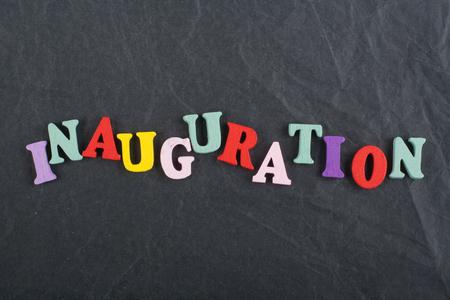 通信: Iinauguration . English word on black board background composed from colorful abc alphabet block wooden letters, copy space for ad text. Learning english concept.