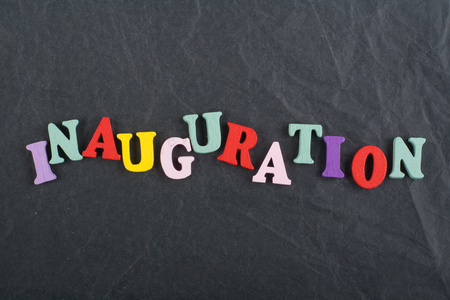 Iinauguration . English word on black board background composed from colorful abc alphabet block wooden letters, copy space for ad text. Learning english concept.