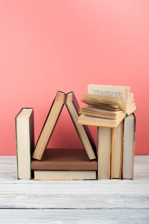 Open book, hardback colorful books on wooden table, red, pink background. Back to school. Copy space for text. Education business concept.