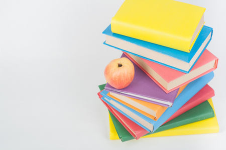 partial: Stack of colorful real books, apple on white background, partial view. Back to school, Copy Space. Education .