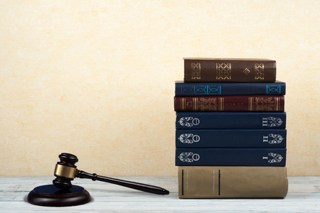 Law concept open book with wooden judges gavel on table in a courtroom or law enforcement office, yellow beige background. Copy space for text. Stock Photo