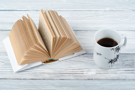 one sheet: Open book, coffee cup and snack on wooden table background.