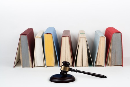 Law concept open book with wooden judges gavel on table in a courtroom or law enforcement office, white background. Copy space for text.