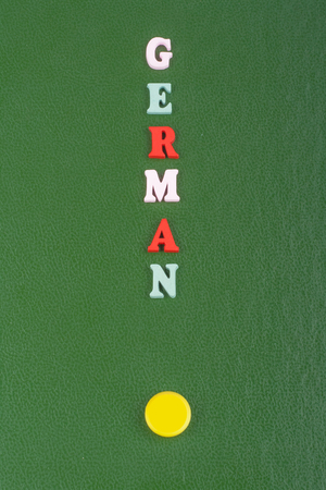 German word on green background composed from colorful abc alphabet block wooden letters, copy space for ad text. Learning english concept.