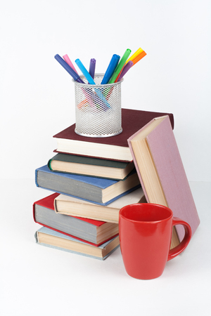 Open book, hardback colorful books on wooden table, white background. Back to school. Pens, pencils, cup. Copy space for text. Education business concept.
