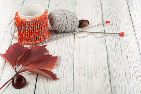 spokes: Autumn still life cup of coffee on wooden table. nitted sweater with autumn leaves, spokes, crochet and coffee mug. Autumn moody style background. Top view.
