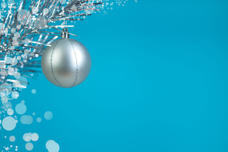 Christmas composition of fir branches and Christmas balls of viburnum on a blue background isolated