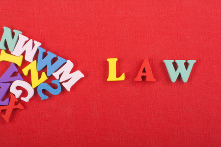 LAW word on red background composed from colorful abc alphabet block wooden letters, copy space for ad text. Learning english concept.