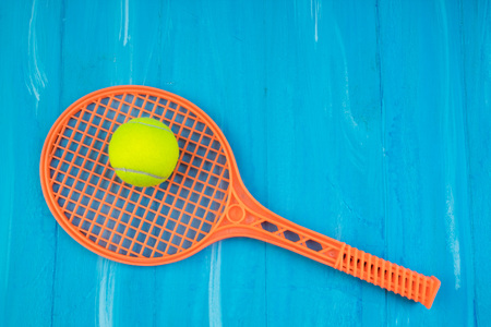 Tennis rackets and ball on blue wooden background. Stock Photo