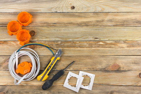 professional repairing implements for decorating and building renovation set on the wooden background, electrician. Electrical tools. Copy space for text. Top view.