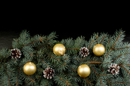 Christmas composition of fir branches and Christmas tree decorations a black background . Top view with copy space.