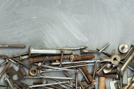 nuts, washers, bolts, screws of various sizes and shapes over the plain background. A set for the mechanic.