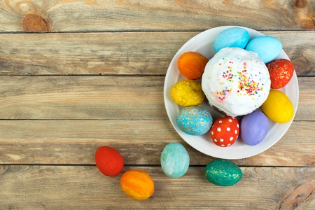 Happy Easter card. Colorful shiny easter eggs cake with white icing and sugar decor on the table decorated in rustic style. Copy space for text. Фото со стока