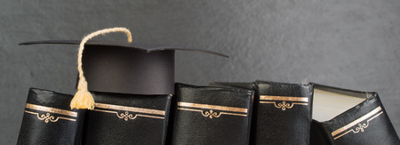 education concept. Graduation hat with gold tassel on the books. Law concep- with copy space for your ad text.
