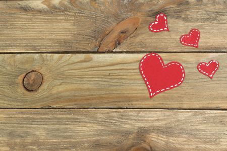 Red paper hearts on a wooden background. Valentines Day. Copy space. Top view.