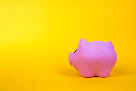 New Years pig. Pink pig on a gold, yellow background with copy space. finance concept 免版税图像
