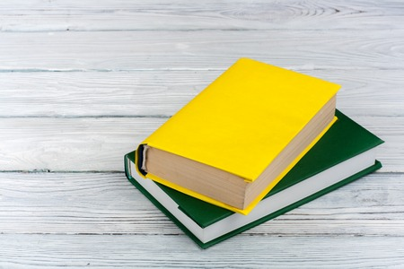 Multi-colored books on a white wooden table. Copy space for text.