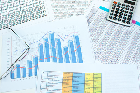 Financial printed paper charts, graphs and diagrams on the table. Top view Foto de archivo