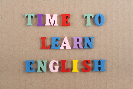 TIME TO LEARN ENGLISH word on paper background composed from colorful abc alphabet block wooden letters, copy space for ad text. Learning english concept.