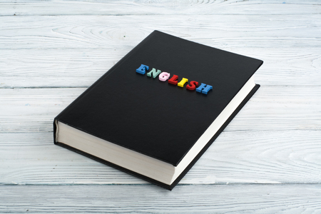 book on a white wooden table, multi-colored letters.
