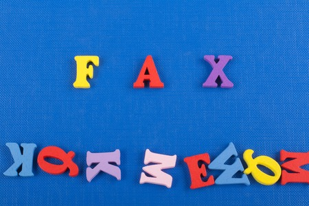 FAX word on blue background composed from colorful abc alphabet block wooden letters, copy space for ad text. Learning english concept. Standard-Bild
