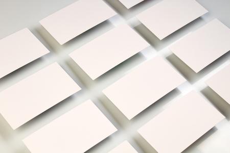 흰색 질감된 종이 배경에 행으로 배열된 수평 명함 스택의 모형.