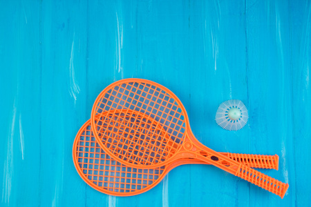 badminton racket and shuttlecock on blue wooden background. Top view.