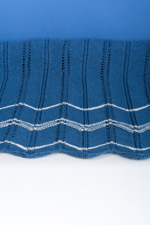 Sweater or scarf fabric texture large knitting. Knitted jersey background with a relief pattern. Braids in knitting . Wool hand- machine, handmade. blue.