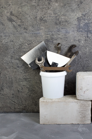 Tools for repair in a construction bucket, bricks on a gray concrete background.. Copy space. Top view.