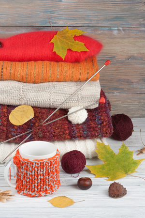 Knitted wool sweaters. Pile of knitted winter, autumn clothes on red, wooden background, sweaters, knitwear, ball, cup, leaf space for text.