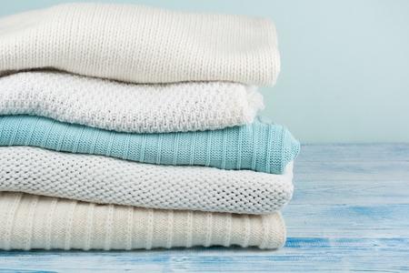 Swetry z dzianiny wełnianej. Kupie zimowe ubrania na zielonym tle drewnianych, dzianiny, miejsca na tekst. Zdjęcie Seryjne
