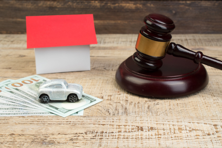 Model of house, car with judges gavel and money on wooden background.