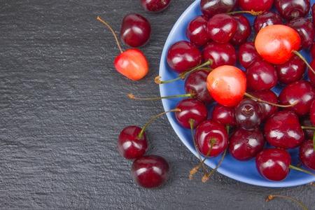 Varios verano Cereza fresca en un recipiente en la mesa de madera rústica. Antioxidantes, dieta de desintoxicación, frutas orgánicas. Vista superior. Bayas