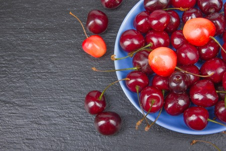 Various summer Fresh Cherry in a bowl on rustic wooden table. Antioxidants, detox diet, organic fruits. Top view. Berries