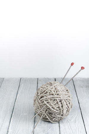 Ball of wool with spokes for handmade knitting on wooden table. Knitting wool and knitting needles. Stock Photo