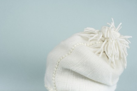 image of white cozy knitted cap with wooden table Stock Photo