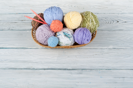 Colored yarn on a white background. Skeins of wool yarn for knitting. Balls of wool with spokes of different colours for handmade knitting on a wooden background with copy space for ad.