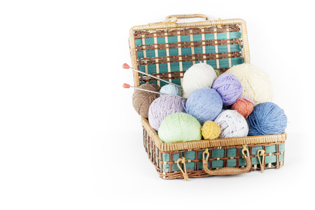 Ball of wool, needles and woolen sweater with spokes for handmade knitting in basket on wooden table.