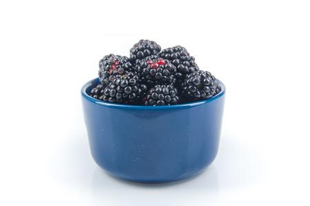 Fresh blackberries, on plate on Isolated white background. Berries