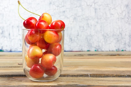 Cherry in a bowl. Fresh yellow cherry. Cherry on a white wooden background. The concept of a healthy diet. Berries Stockfoto