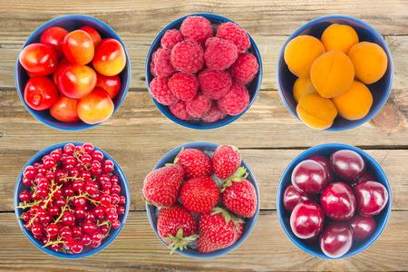 Berries on Wooden background, bowl of Cherry, currant, blueberries, gooseberries, raspberries, blackberries, strawberries, apricots. Stockfoto