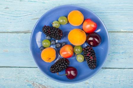 Various summer Fresh berries in a bowl on rustic wooden table. .Antioxidants, detox diet, organic fruits. Top view. Berries