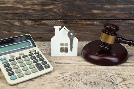 wooden house, calculator, judges gavel on wooden background. purchase, sale of real estate. housing.