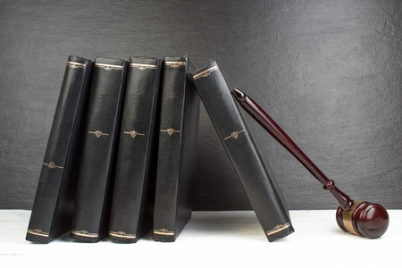 Law concept - Open law book with a wooden judges gavel on table in a courtroom or law enforcement office isolated on white table. Copy space for text.