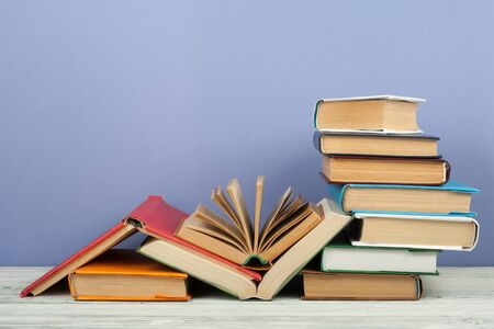 Open book, hardback colorful books on wooden table. Back to school. Copy space for text. Education business concept.